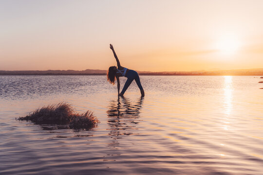 Full length back view of unrecognizable focused female in activewear practicing Parivrtta Trikonasana twisted yoga pose while standing in water of peaceful lake against sundown sky