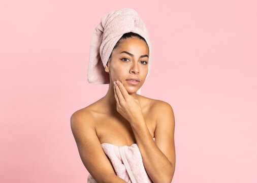 Charming young ethnic bare shouldered female with bath towel on head and perfect olive skin looking at camera touching skin standing against pink background while representing beauty and skincare concept
