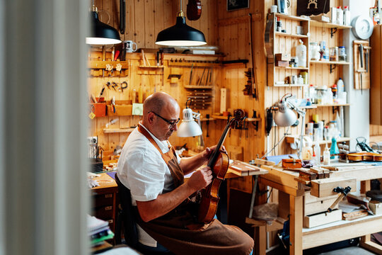 Side view of mature male luthier in apron and glasses sitting on chair and holding restored violin while working in workshop