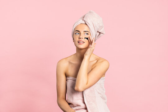 Young woman applying charcoal mask on face enjoying spa day while standing looking away on pink background