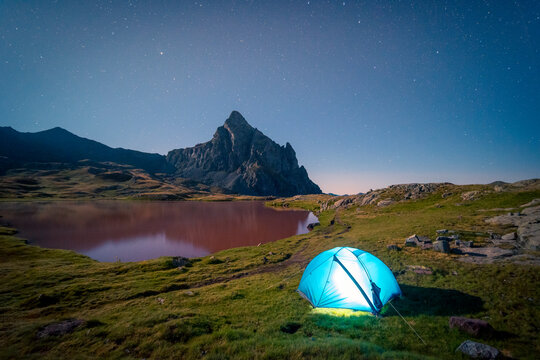 Spectacular view of camping tent placed on meadow near lake in mountainous area under starry sky in long exposure