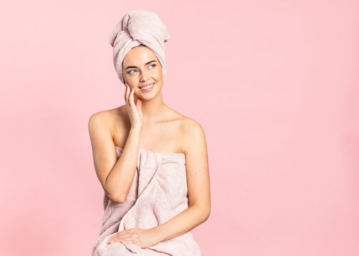 Delighted young bare shouldered female wrapped in towels touching cheek and smiling while enjoying healthy smooth skin after spa procedure