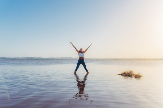 Full body of unrecognizable slim female in activewear standing in Five Pointed Star Pose with arms up in lake water while practicing yoga in summer evening