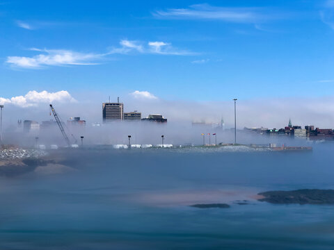 Saint John New Brunswick in low fog along the port with sunny skies