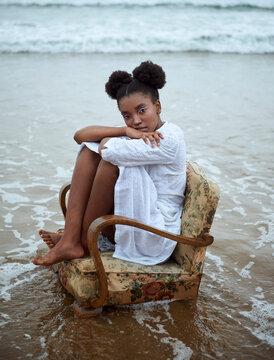 Portrait of thoughtful teenage girl sitting on armchair on beach