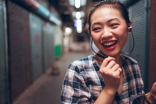 Joyful young Asian female student in casual clothes communicating with friends through headset while standing on blurred urban background