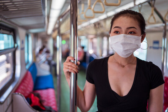Ethnic female wearing protective mask traveling by train during coronavirus outbreak