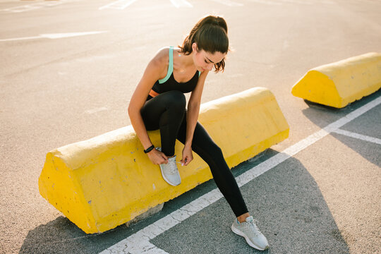Full body of young slim female runner in black sportswear sitting on concrete border on paved street and tying laces on sneakers while preparing for jogging