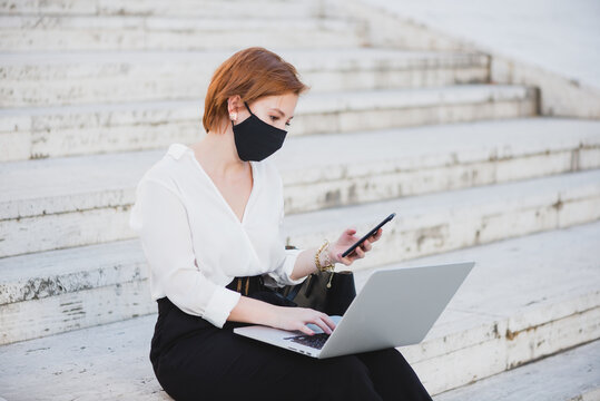 Concentrated businesswoman in elegant clothes and medical mask sitting on stairs on street and working on remote project while using laptop and smartphone