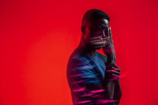 Serious confident young African American male with colorful neon lights on face looking at camera against red background