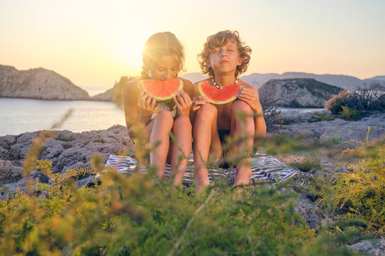 Two children eating watermelon with a expression of pleasure while sitting on a blue and white striped towel on a rock facing the sea at sunset