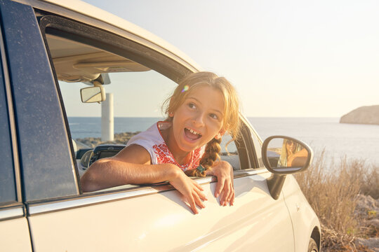 Blonde girl sticking her head out of the window of a car parked in front of the sea with a happy expression and her mother's reflection in the side mirror of the car