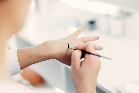 Unrecognizable female makeup artist standing in beauty salon and applying black eyeliner on hand