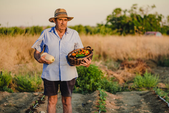 Aged male farmer standing barefoot with wicker basket of fresh fruits and vegetables on garden bed and looking at camera