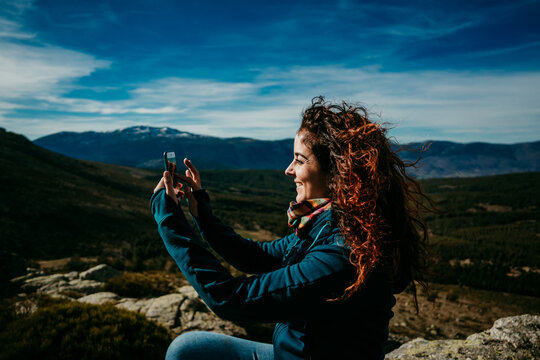 Side view of glad woman using smartphone to take photos of Puerto de la Morcuera mountain ridge on cloudy day in Spain
