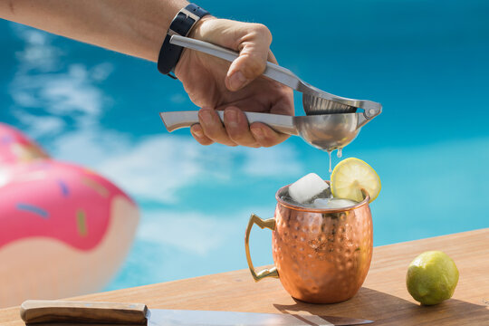 Crop anonymous man with squeezer adding lime juice into copper cup with Moscow mule cocktail near swimming pool in summer day