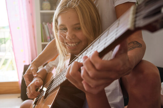 Blonde girl playing guitar while smiling with a woman sitting with her on a couch and teaching her in a house