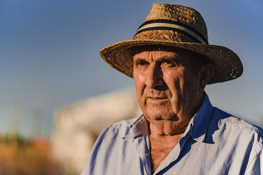 Confident elderly male farmer in straw hat looking away while standing against blurred background of agricultural field in sunny summer day