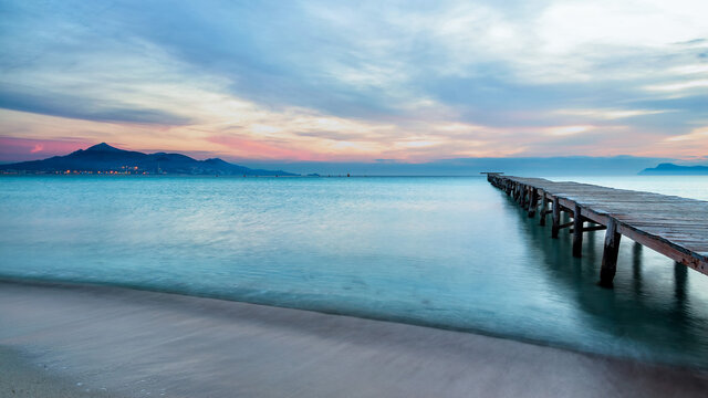 Majestic scenery of wooden quay leading to calm sea water under sunset sky in Playa de Alcudia in long exposure