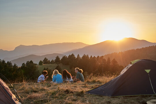 Back view of group of traveling friends relaxing on grass near camping tent and enjoying summer vacation during sundown in highland area