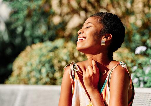 Happy ethnic woman enjoying sunny day in park