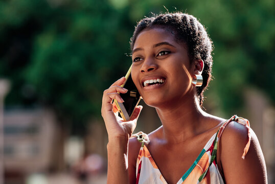 Delighted young African American female in stylish colorful outfit discussing news with friend during phone call while spending sunny summer day in park