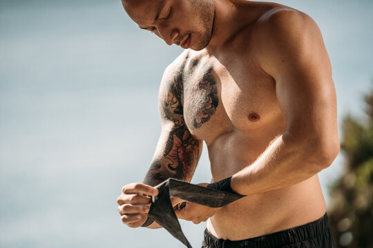 Crop male athlete with strong body standing in park and wrapping wrists with bandages before training