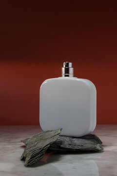 White cosmetic spray bottle arranged on stones on marble surface against red wall