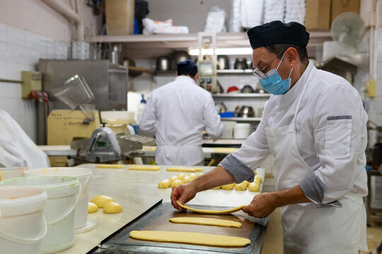 Side view of mature male cook in medical mask preparing raw dough for baking tasty pastry in bakehouse during coronavirus