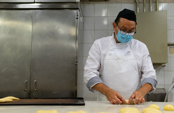 Mature male cook in medical mask and uniform making buns from raw dough while working in kitchen of bakehouse during COVID 19