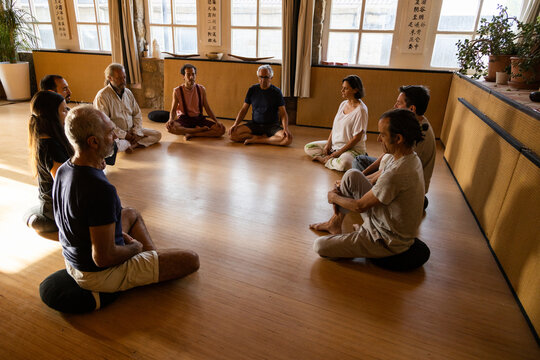 Group of diverse people with instructor sitting on floor and practicing meditation during traditional chi kung session in studio