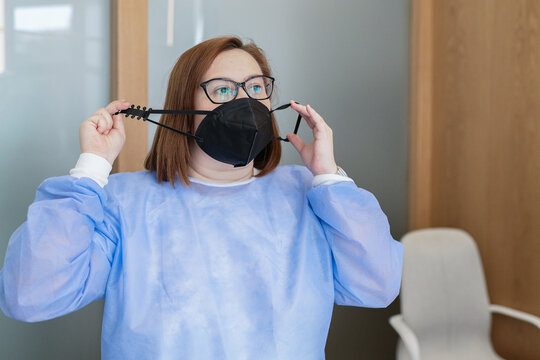 Female medical worker in blue uniform and eyeglasses putting on black protective mask with adjustable strap while working in modern clinic during coronavirus pandemic