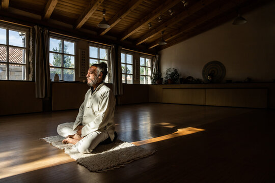 Full body side view of focused bearded ethnic senior male practicing chi kung meditation in lotus position in dark studio