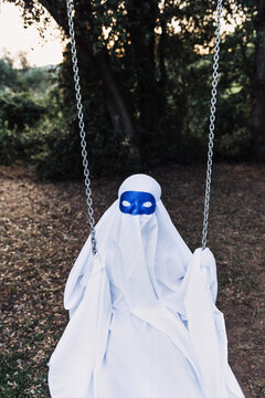 Unrecognizable kid in white ghost costume swinging and playing on playground during Halloween holiday