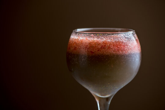 Refreshing strawberry alcohol cocktail in glass in studio on brown background