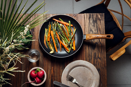 Carrot, asparagus and zucchini sauteed in the pan, on the table ready to eat. Simple and healthy vegan eating concept