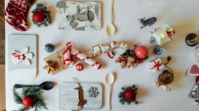 Top view composition with decorative snowflake and wooden fox figure hanging on pine tree branch arranged near spoon on table during Christmas celebration