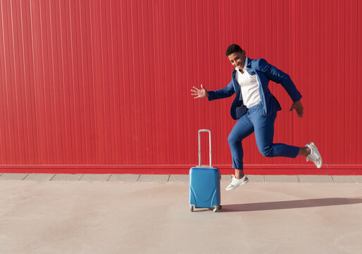 Full length side view of happy young African American male entrepreneur in stylish outfit with suitcase screaming and jumping near red wall while celebrating business success