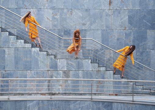 Portrait of women in yellow dress leaning on railings in city