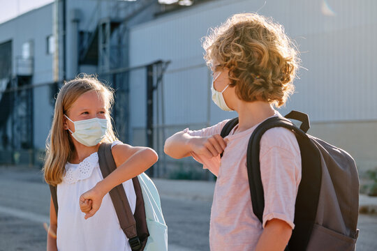 Two children with school bags and masks greeting each other with a gesture of touching elbows outdoors