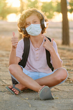 Vertical photo of a blond boy with mask and school bag sitting cross-legged while listening to music and making a gesture of being well by raising his thumb while facing the camera