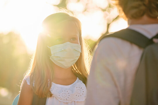 Sunlight illuminating the face of a girl wearing a mask in front of a boy with a schoolbag outdoors in a park