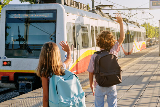 Two children with black school bags on their backs greeting a train as it leaves the track from a station platform