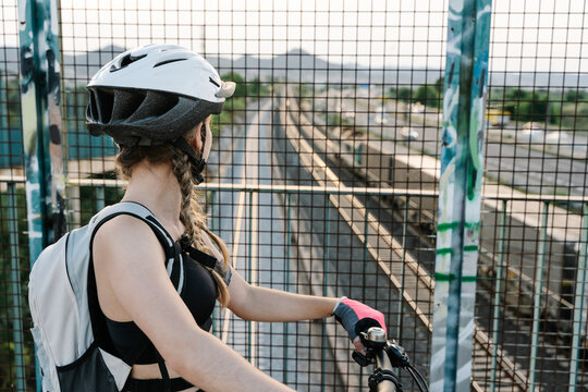 Back view of crop unrecognizable female bicyclist in protective helmet and gloves standing near grate fence on bridge over road with blurred hills in background