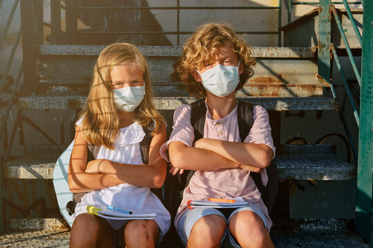 Two blond kids with masks and school bags sitting on an outside staircase with their arms crossed in denial while facing the camera