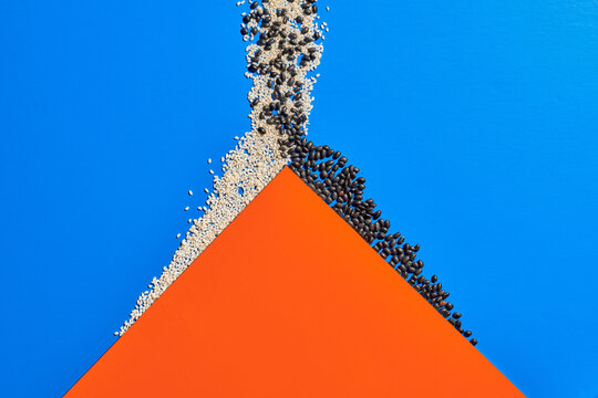 Top view of orange paper in shape of mountain placed on blue background with white and black grain