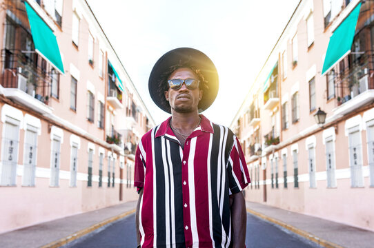Low angle of confident young African American male in stylish stripped shirt and sunglasses with hat looking at camera while standing against blurred urban street