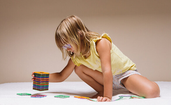 Side view of adorable preschool girl in eyeglasses sitting on floor and playing with colorful educational blocks