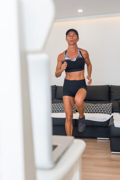 Serious female athlete in sportswear watching video on laptop and running on floor at home during intense cardio workout
