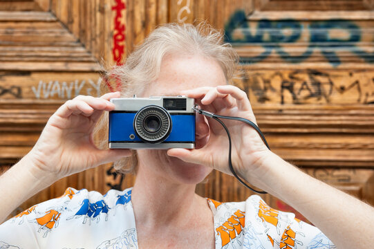 Middle aged female traveler standing on street and taking picture on vintage photo camera